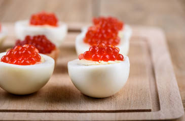 Selective focus. Red caviar on halves of hard-boiled chicken eggs on a cutting board