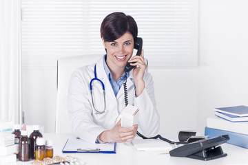 Smiling young female doctor talking on a telephone