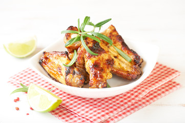 Teriyaki chicken wings. Baked chicken  with fresh rosemary. Homemade food. Symbolic image. Concept for a tasty and healty dish. Bright wooden background. Copy space.