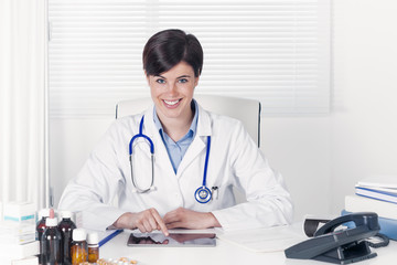 Pretty confident young female doctor seated in her office