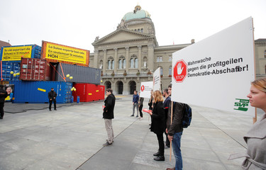 Counter protestors of the youth organisation of the SVP stand beside as Swiss economic association Economiesuisse placed containers in front of the Bundeshaus in Bern