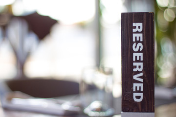 Reserved wooden Card Plate on the Table with Blurry background. Reservation Seat at restaurant. - leisure, people and service concept
