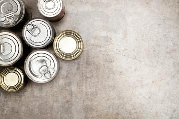 Botes de conserva de comida sobre fondo gris rústico. Vista superior. Copy space