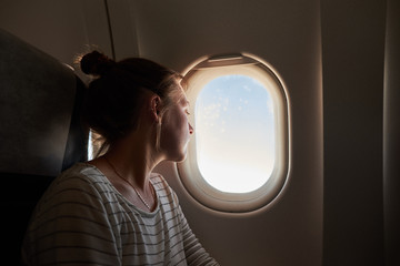 Girls looking out the window of the plane.