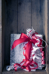 Christmas present with a red ribbon in a wooden box background