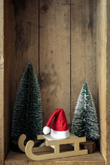 Christmas decoration sledge with Santa Claus hat and trees in a wooden box background