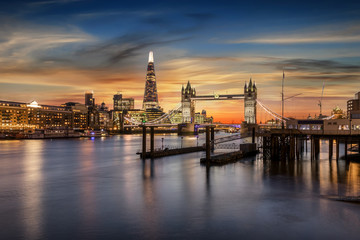 Fotomurales - Blick auf die Tower Bridge an der Themse und die beleuchtete, urbane Skyline von London bei Sonnenuntergang, Großbritannien