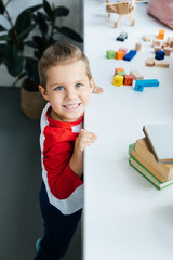 high angle view of child standing at surface with books and colorful blocks at home