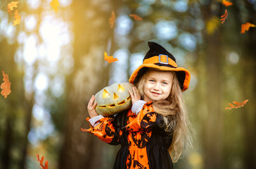 Cute little girl in witch costume for the holiday of Halloween. She holds a pumpkin in her hands and stands in the park. Wall mural