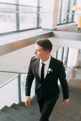 Stylish minimalism in the image of the groom. Black color and European wedding. The preparations of the groom, hotel