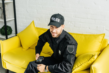 happy young policeman with smartphone sitting on yellow couch and looking at camera