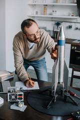 handsome engineer modeling and measuring rocket at home