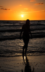 Foto op Canvas Akt Silhouette of beautiful naked young woman posing in the sea