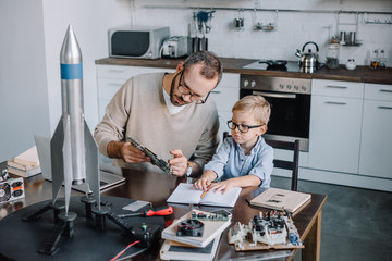 father and son repairing microcircuit at home Wall mural