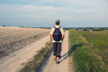 Man traveler with a backpack walking along a dirt road