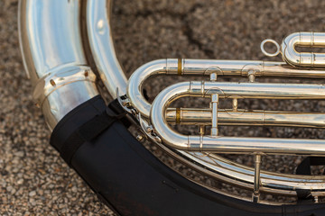 well used sousaphone resting on the ground during a marching band rehearsal