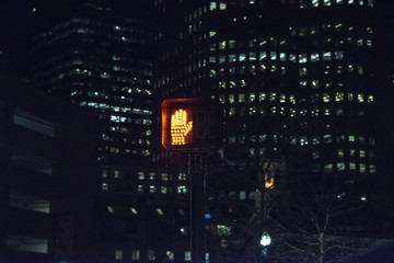 'don't walk' illuminated hand sign at night