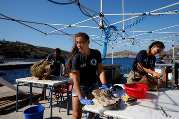 Students of the Department of Conservation of Antiquities and Works of Art Giorgos Agavanakis,  Helen Margarita Bardas and Eirini Mitsi, work on amphorae retrieved from shipwreck sites on the island of Fournoi