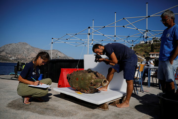 Student of the Department of Conservation of Antiquities and Works of Art Giorgos Agavanakis, takes pictures as fellow student Eirini Mitsi, takes notes on an amphora retrieved from a shipwreck site on the island of Fournoi