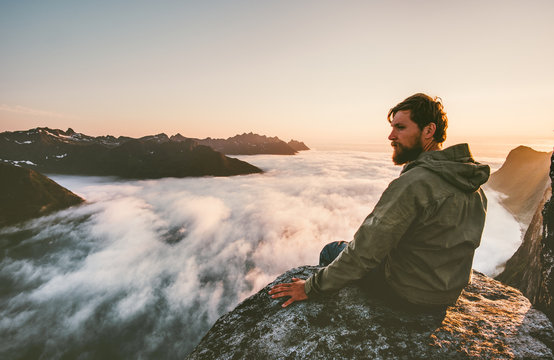 Traveler man sitting alone on the edge cliff  mountains above clouds travel adventure lifestyle weekend getaway vacations in Norway