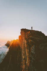 Traveler on cliff hiking alone sunset mountain adventure outdoor active vacations traveling lifestyle getaway