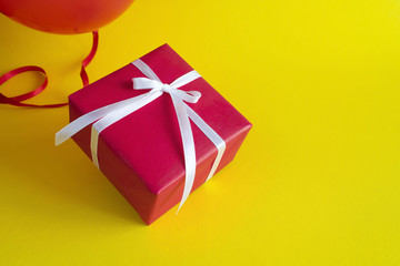 Red gift box with red balloon on yellow background. Copy space.