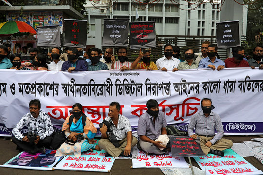 Journalists hold banners and placards as they protest against the newly passed Digital Security Act  in front of the Press Club in Dhaka