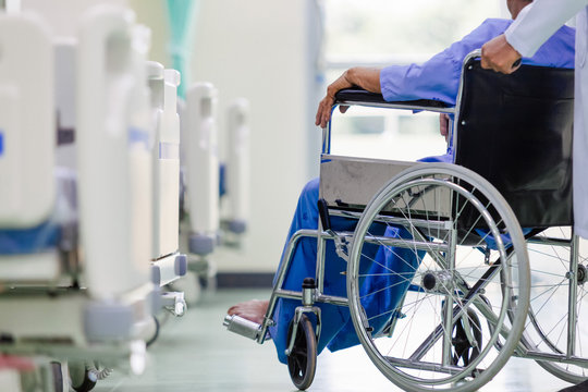 Asian patient in wheelchair sitting in hospital with Asian doctor.