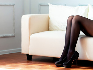 Long woman legs in black tights on white sofa.