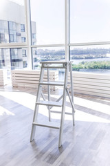 White wooden stepladder in a new apartment with french windows