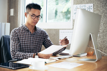 Young concentrated Asian man in checked shirt and glasses sitting at office desk and analyzing financial papers