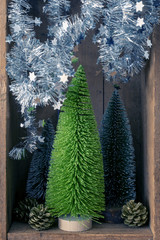 Christmas decoration trees and pinecones in a wooden box background