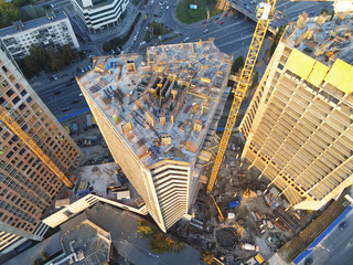 High tower building construction site. Bug industrial crane. Aerial drone view. Metropolis city development