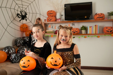 Portrait of smart pretty Caucasian little girls with Halloween makeup sitting with pumpkins in decorated room and smiling at camera happily Wall mural