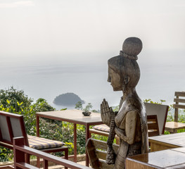 Сarved wooden sculpture of a woman welcoming in a cafe. Thai greeting wai. Beautiful seaview from the table in the restaurant.