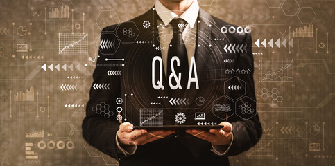 Q and A with businessman holding a tablet computer on a dark vintage background