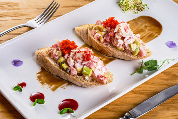 Two delicious shrimp sandwiches with tomato and red caviar. Homemade sandwiches served on a white plate with knife and fork decorated with sauces and herbs.