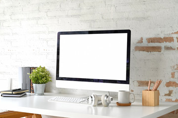 Loft workplace with mockup blank screen desktop computer and home office accessories
