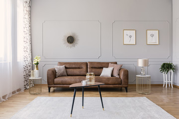 Wooden table on carpet in front of leather sofa in grey living room interior with posters. Real photo