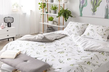 Green plant pattern on white bedding and pillows on a bed in a nature loving bedroom interior. Real photo.