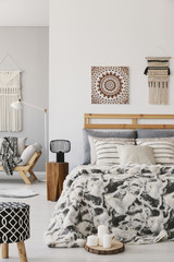 Patterned stool and lamp next to bed with cushions in scandi bedroom interior with poster. Real photo