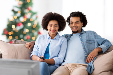 people, family and leisure concept - happy african american couple watching tv over christmas tree lights background