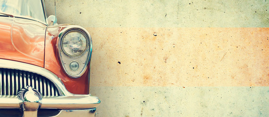 The headlight of the old beautiful car on the background of a concrete wall. Copy space. Concept banners repair, sale of cars. Wall mural