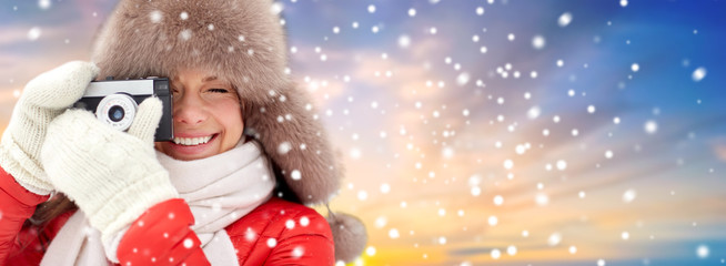 photography, technology and winter concept - happy woman in fur hat taking picture by film camera outdoors over snow and sky background