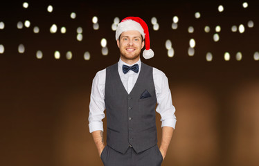 celebration, people and holidays concept - happy man in santa hat and suit at christmas over garland lights background