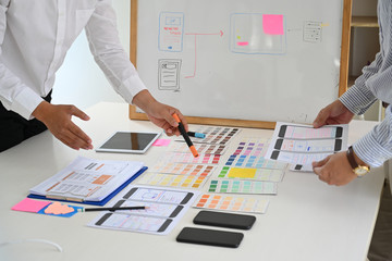 Wall Mural - Web designer teamwork concept UX UI designer planning layout application for mobile phone mockup on white board