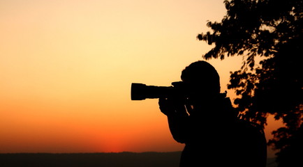 silhouette photographer taking photo of sunset light