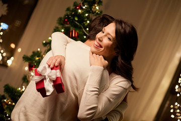 winter holidays and people concept - happy couple with christmas gift hugging at home