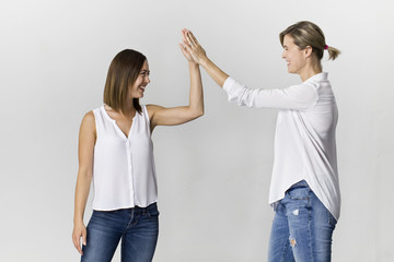 Happy friends are greeting and giving a five at white background. Two beautiful young women