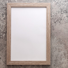 Wooden empty mockup frame on the background of an old gray concrete wall